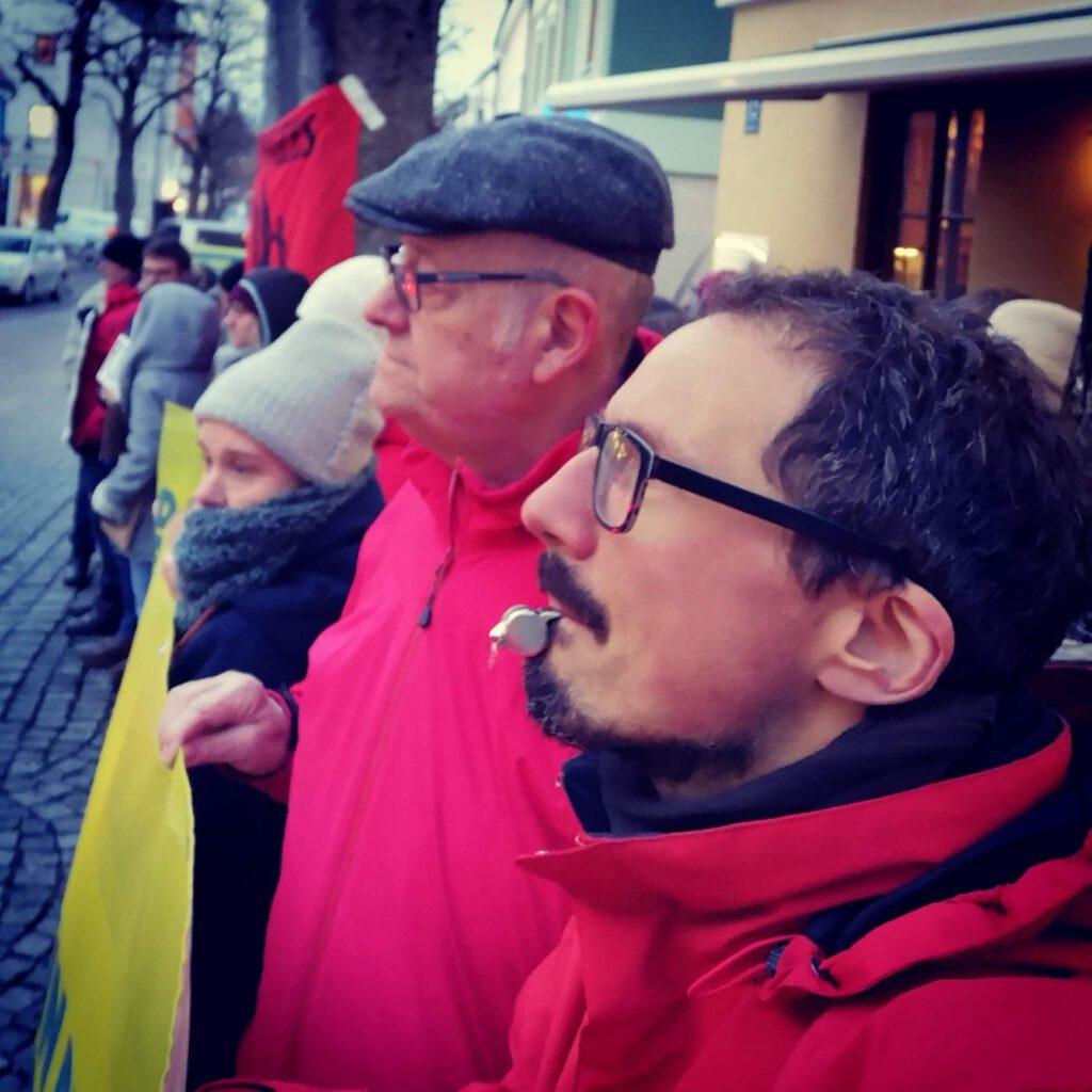 Bernhard Gruppe als Teil einer Gruppe von Demonstrierenden mit einer Trillerpfeife im Mund und einem Transparent.