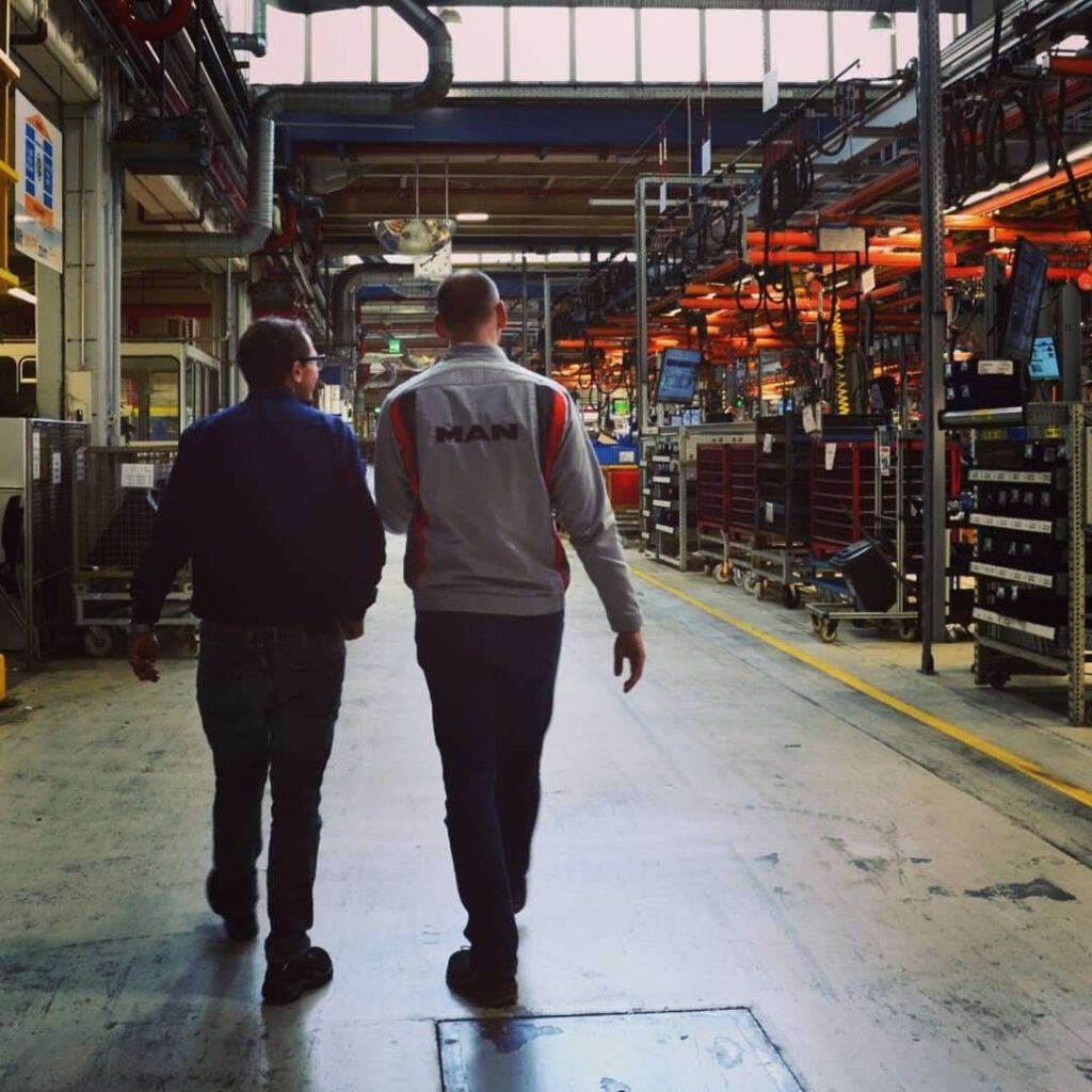 Bernhard Goodwin auf dem Weg durch eine Werkshalle von MAN geführt von einem Mitarbeiter der Firma.