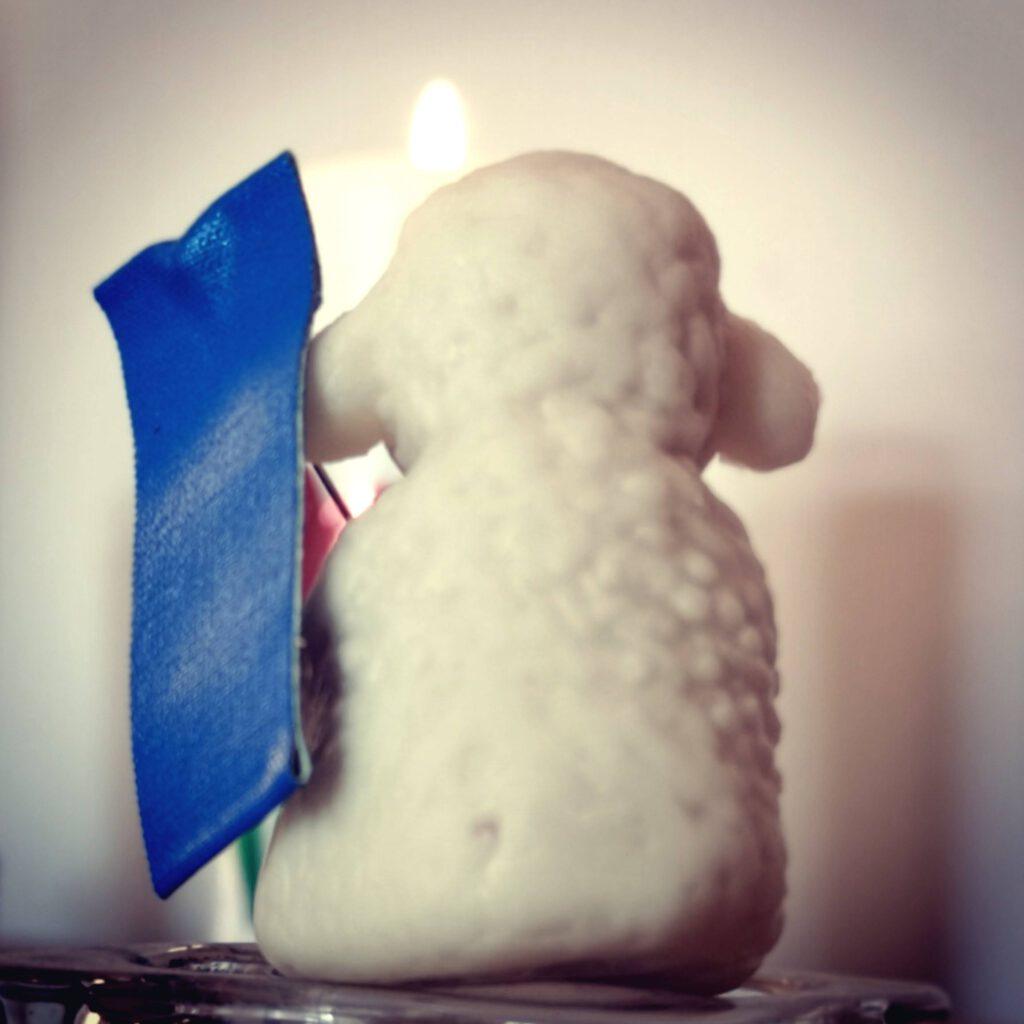 Detailaufnahme eines Marzipanlammed mit einer blauen Fahne und einer Kerze im Hintergrund.