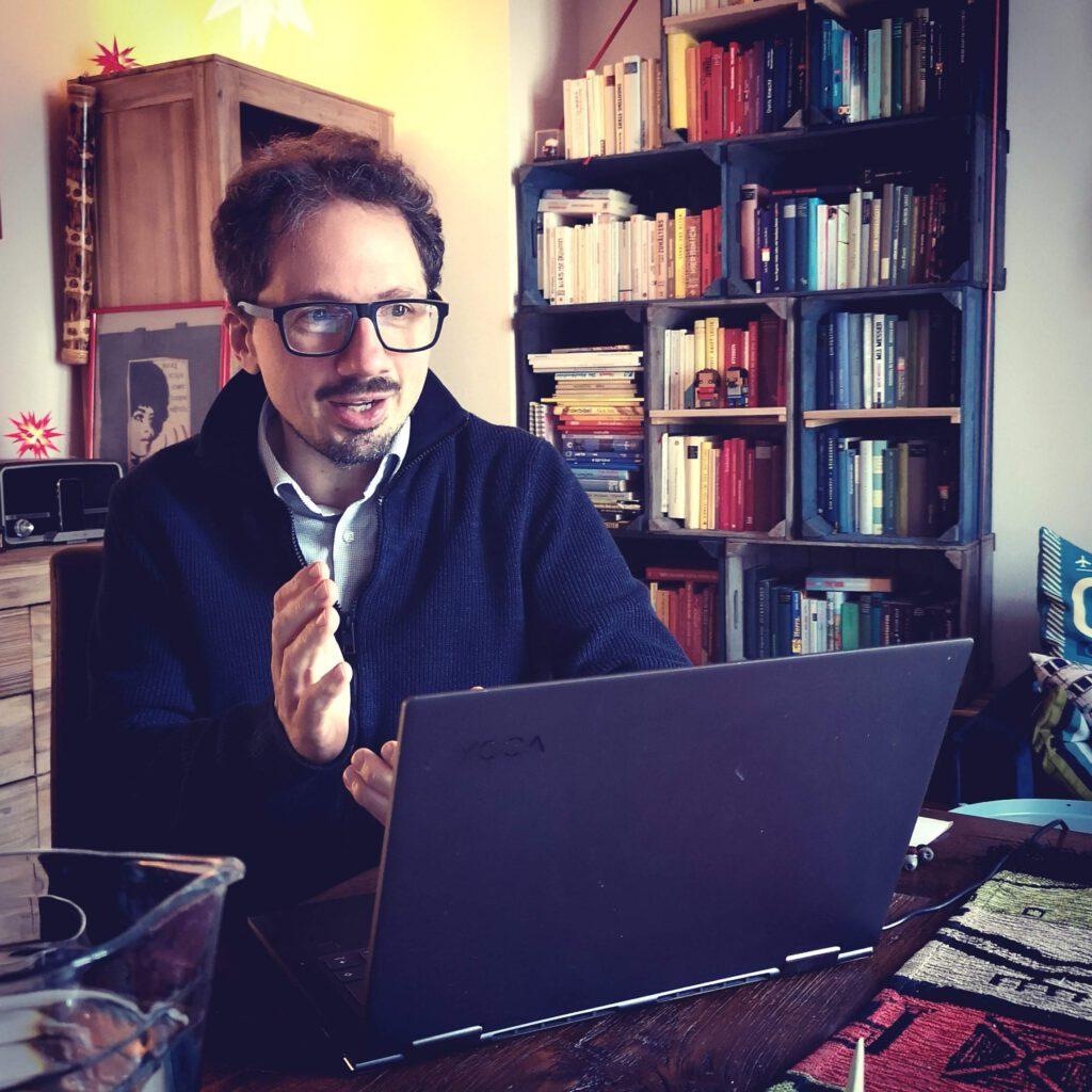 Bernhard Goodwin spricht in die Webcam seines Laptops im Wohnzimmer seiner Wohnung am Esstisch vor einem Bücherregal.